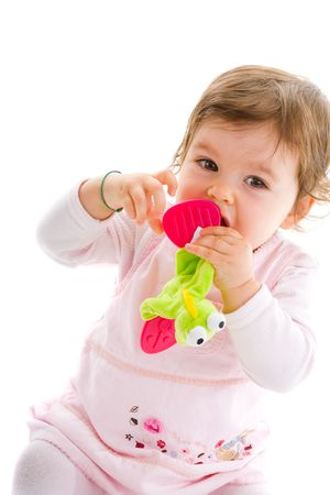 Happy baby girl sitting on floor playing with soft toy, smiling, isolated on white background. photo