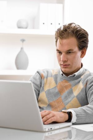 Young man working on laptop computer at home. Stock Photo - 5982721