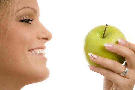 Closeup portrait of beautiful girl holding a green apple, smiling. Side view, isolated on white background. photo
