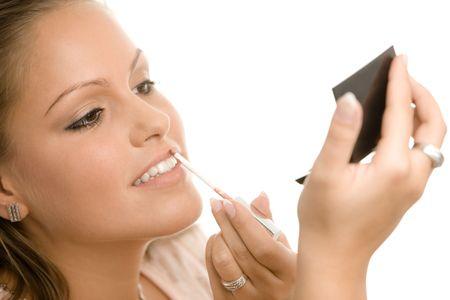 mujer maquillandose: Hermosa mujer joven aplicar maquillaje, poniendo en el forro de labio, sosteniendo el espejo. Aislado sobre fondo blanco.