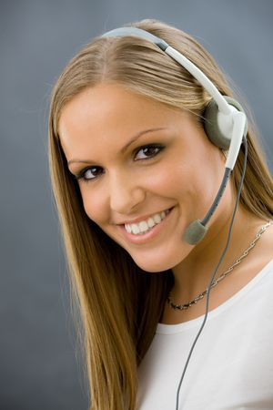 Studio portrait of happy young female customer service operator talking on headset. Isolated. photo