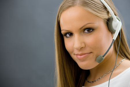 Studio portrait of young female customer service operator talking on headset. Isolated. photo