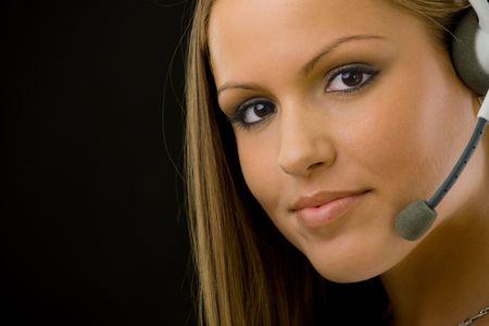telephone headsets: Young feliz cliente hermoso servicio Operador chica en el kit manos libres port�til, sonriente, aislado sobre fondo negro. Foto de archivo