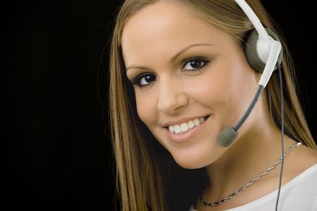 customer service: Young happy beautiful customer service operator girl in headset, smiling, isolated on black background.