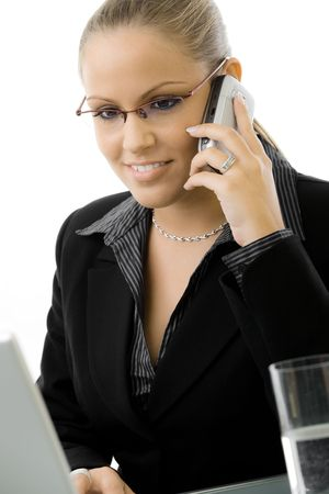 Young businesswoman working on laptop computer and calling on mobile phone, isolated on white. photo