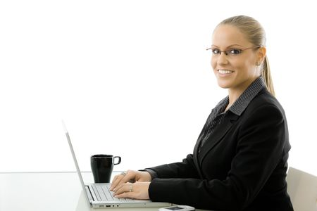 Happy young businesswoman sitting at desk working on laptop computer, smiling, isolated on white background. photo