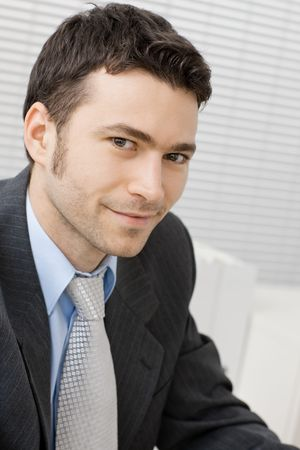 Portrait of happy smiling young businessman at office. photo