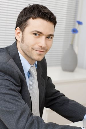 Portrait of happy smiling young businessman at office. Stock Photo - 5982963
