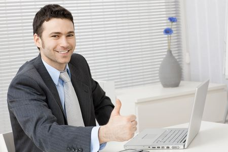gratified: Happy young businessman showing success with thumb up at office, smiling. Stock Photo