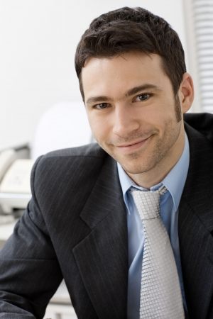Portrait of young and happy businessman at office desk, smiling. photo