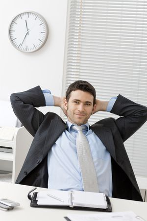 Businessman sitting at office desk with satisfied expression, looking at camera, smiling. photo