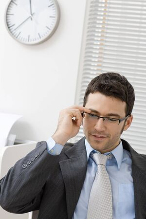 Young businessman taking off his glasses, smiling. Stock Photo - 5982830