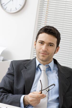 Young businessman sitting behind office desk, holding glasses, smiling. photo