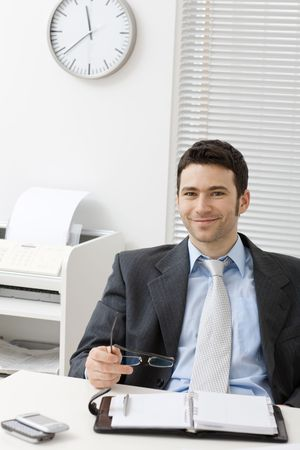 fulfilled: Happy young businessman working at desk at office, smiling.