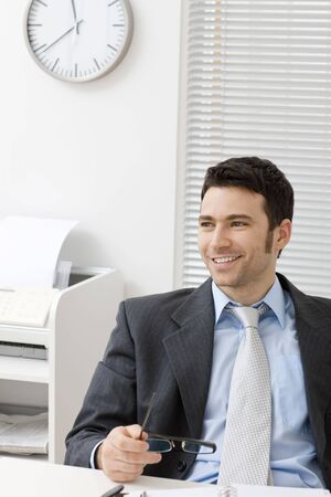 Happy businessman sitting behind office desk, holding glasses, smiling. photo