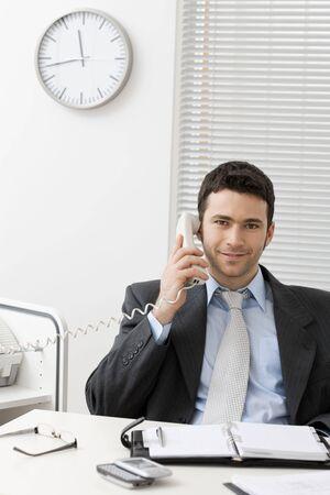 Businessman sitting at desk in office, talking on landline phone, smiling. photo