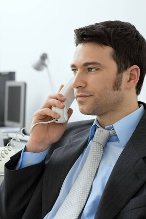 Closeup of businessman sitting at desk in office, talking on landline phone. photo