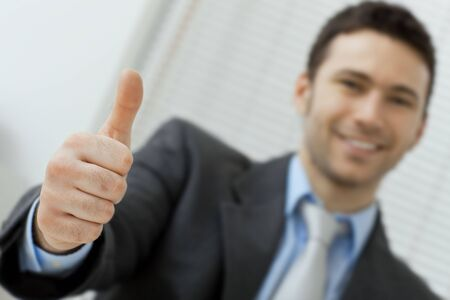 Businessman showing OK sign with his thumb up. Selective focus on hand. Stock Photo - 5982815