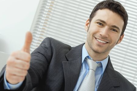 Businessman showing OK sign with his thumb up. Selective focus on face. Stock Photo - 5982751