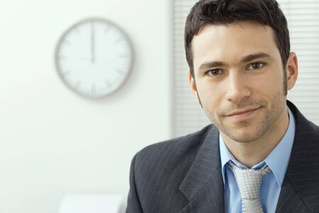 motivated: Portrait of young handsome businessman at office, smiling.