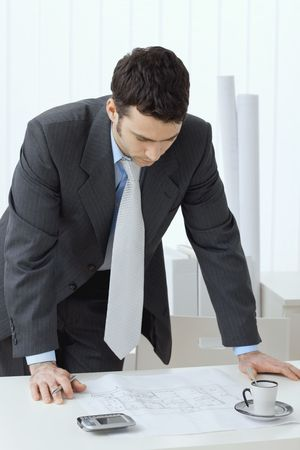 Architect wearing grey suit leaning on office desk with floor plan on it. Looking down. photo