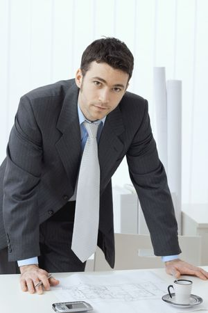 Architect wearing grey suit leaning on office desk with floor plan on it. Looking at camera. photo