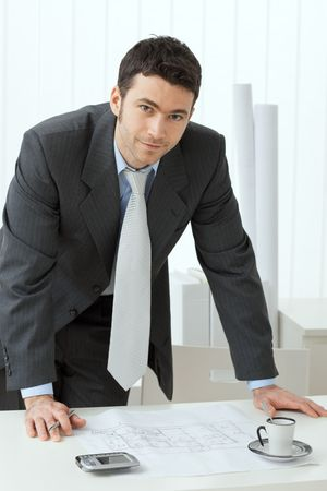 Architect wearing grey suit leaning on office desk with floor plan on it. Looking at camera, smiling. photo