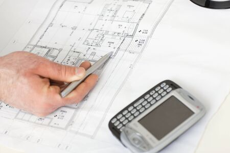 Architects hand pointing with pen to flooor plan on desk with mobile phone on it. photo