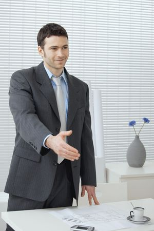 Young businessman in grey suit and blue shirt, standing with open hand, ready to set a deal. Stock Photo - 5982980