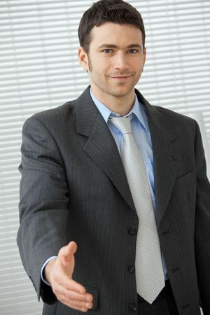Young businessman in grey suit and blue shirt, standing with open hand, ready to set a deal. photo