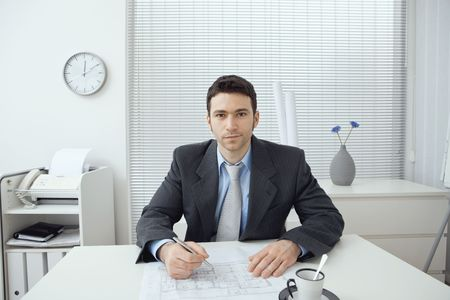 Young architect working at office desk, smiling. photo