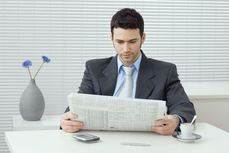 Young businessman having coffee break, sitting at office desk and reading newspaper. photo