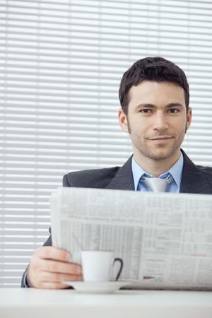 Young businessman having coffee break, sitting at office desk and reading newspaper. Stock Photo - 5982836