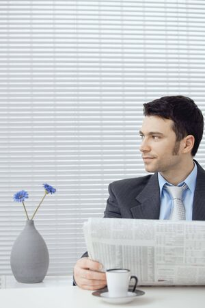 Young businessman having coffee break, sitting at office desk and reading newspaper. Copy space. photo