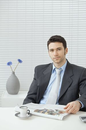 Young businessman having coffee break, sitting at office desk and reading newspaper. Copy space. Stock Photo - 5983012