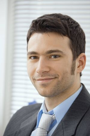 fulfilled: Portrait of smiling young businessman at office. Stock Photo