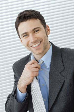 Portrait of happy young businessman at office wearing grey suit and blue shirt, adjusting his tie, smiling. photo