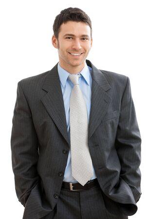 Hombre de negocios feliz de pie con las manos en el bolsillo, mirando a cámara, sonriendo. Aislado sobre fondo blanco. Foto de archivo
