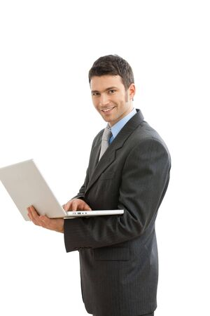 Businessman using laptop computer, standing, smiling. Isolated on white background. photo