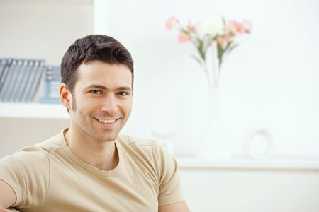 hombre sentado: Joven apuesto hombre feliz en casa, sonriendo.