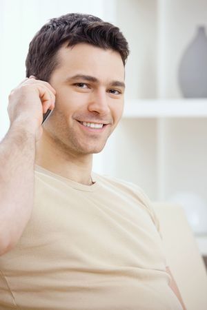 Young man talking on mobile phone at home. Stock Photo - 5982762