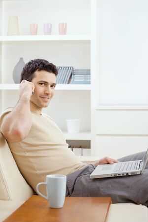 teleworking: Young man sitting on sofa and teleworking from home.