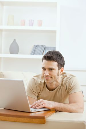 telecommuting: Happy young man laying on sofa at home using laptop computer, smiling. Stock Photo