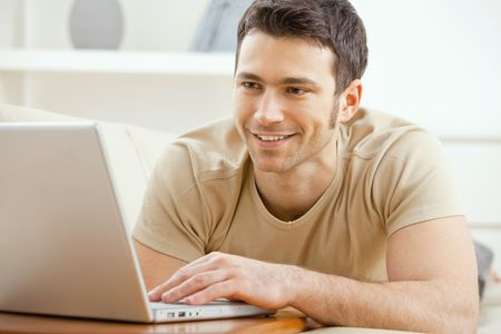 chat room: Happy young man laying on sofa at home using laptop computer, smiling. Stock Photo
