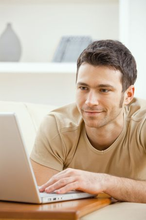 telework: Happy young man laying on sofa at home using laptop computer, smiling. Stock Photo