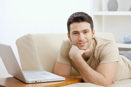 Happy young man laying on sofa at home using laptop computer, smiling. photo