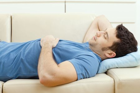 Young handsome man sleeping on couch at home, side view. photo