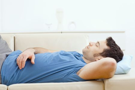 lying on couch: Young handsome man sleeping on couch at home, side view. Stock Photo