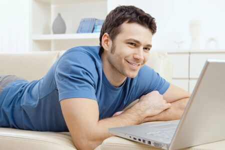 Happy young man laying on sofa and using laptop computer at home, smiling. photo