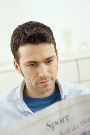Handsome young man sitting on couch at home reading sport news in newspaper. Stock Photo - 5983000